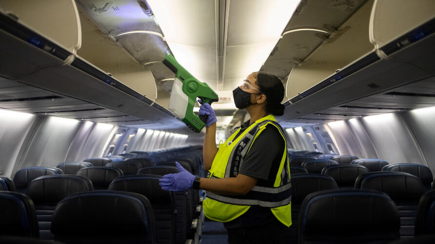 FILE PHOTO: Worker demonstrates use of an electrostatic disinfectant sprayer on United Airlines plane at IAH George Bush Intercontinental Airport in Houston
