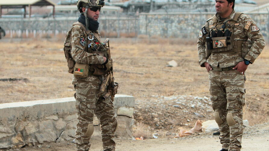Afghan National Security Forces keep watch outside of a military compound after a car bomb blast on the outskirts of Ghazni city