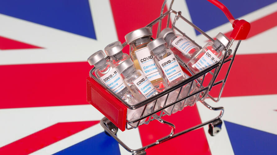 """FILE PHOTO: A small shopping basket filled with vials labeled  """"COVID-19 - Coronavirus Vaccine""""  is placed on a UK flag"""