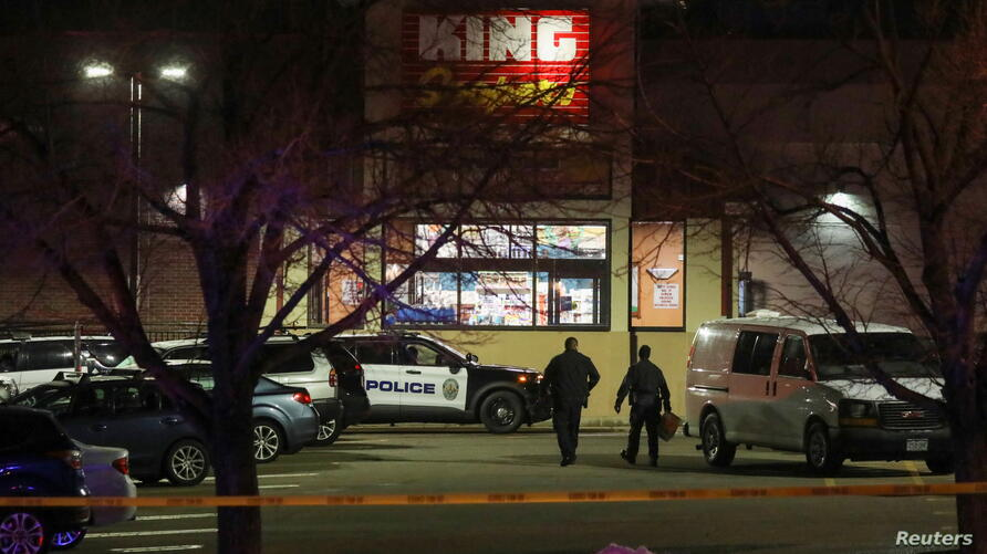 Law enforcement officers investigate the site of a shooting at a King Soopers grocery store in Boulder