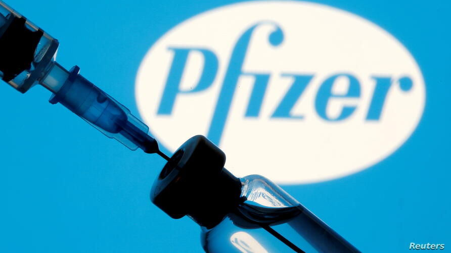 FILE PHOTO: Vial and sryinge are seen in front of displayed Pfizer logo
