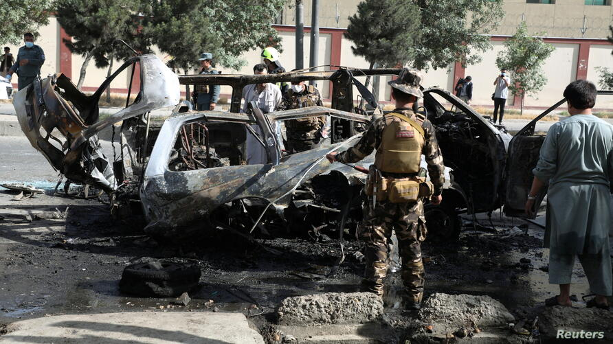 Afghan security forces inspect the wreckage of a passenger van after a blast in Kabul, Afghanistan