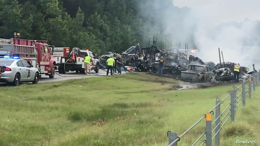 Emergency personnel work at the accident site as smoke rises from the wreckage after about 18 vehicles slammed together on a rain-drenched Alabama highway during Tropical Storm Claudette, in Butler County, Alabama