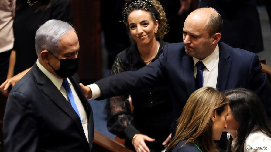 Head of Oposition Benjamin Netanyahu and Israel Prime Minister Naftali Bennett gesture following the vote on the new coalition at the Knesset, Israel's parliament, in Jerusalem