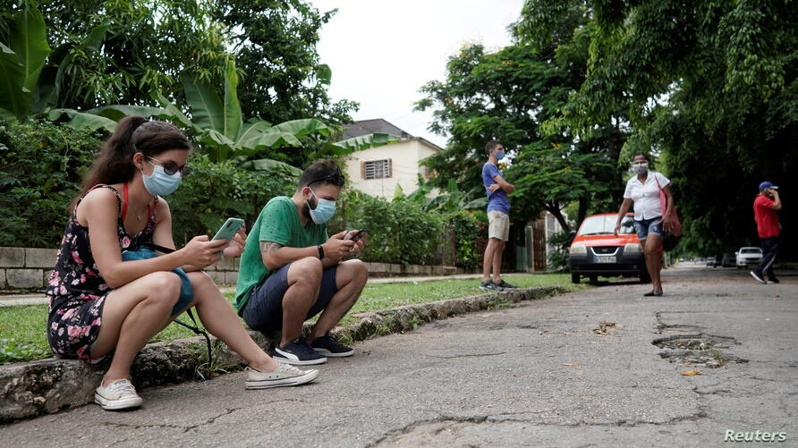 People connect to the internet at a hotspot in a public park in Havana