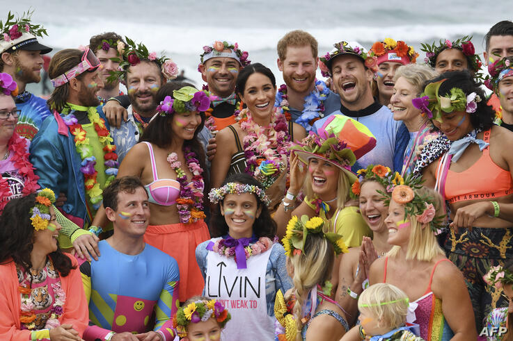 "Britain's Prince Harry (C-R) and his wife Meghan, the Duchess of Sussex (C-L) pose during a ""Fluro Friday"" session run by OneWave, a local surfing community group who raise awareness for mental health and wellbeing, at Bondi Beach in Sydney"