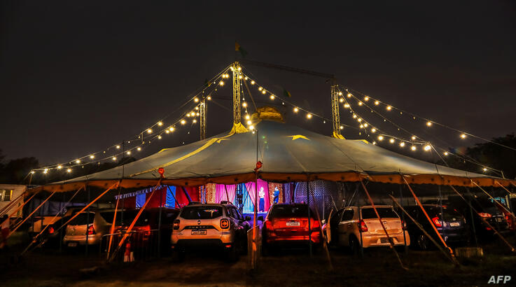 TOPSHOT - People in their cars attend a show at the Las Vegas Circus in Porto Alegre, southern Brazil late on June 20, 2020. -…