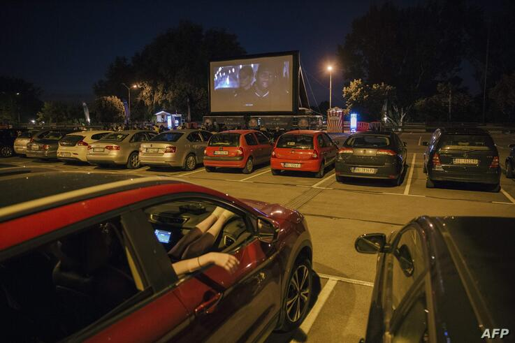 People watch a movie from their cars at an open-air cinema in Belgrade on June 24, 2020, amid the novel coronavirus pandemic. -…