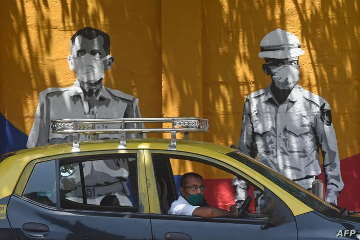 A taxi driver drives past a wall mural painted to thank frontline workers fighting against the spread of the COVID-19…