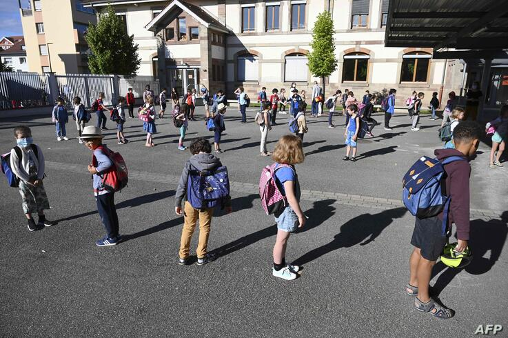 Children queue to enter their classrooms at the Ziegelau elementary school in Strasbourg, eastern France, as primary and middle…