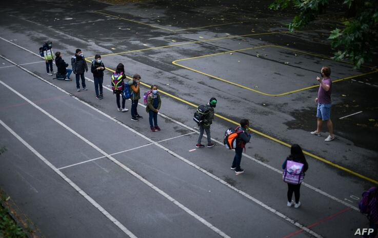 A teacher instructs students as they line up for the entrance at the schoolyard of the Petri primary school in Dortmund,…
