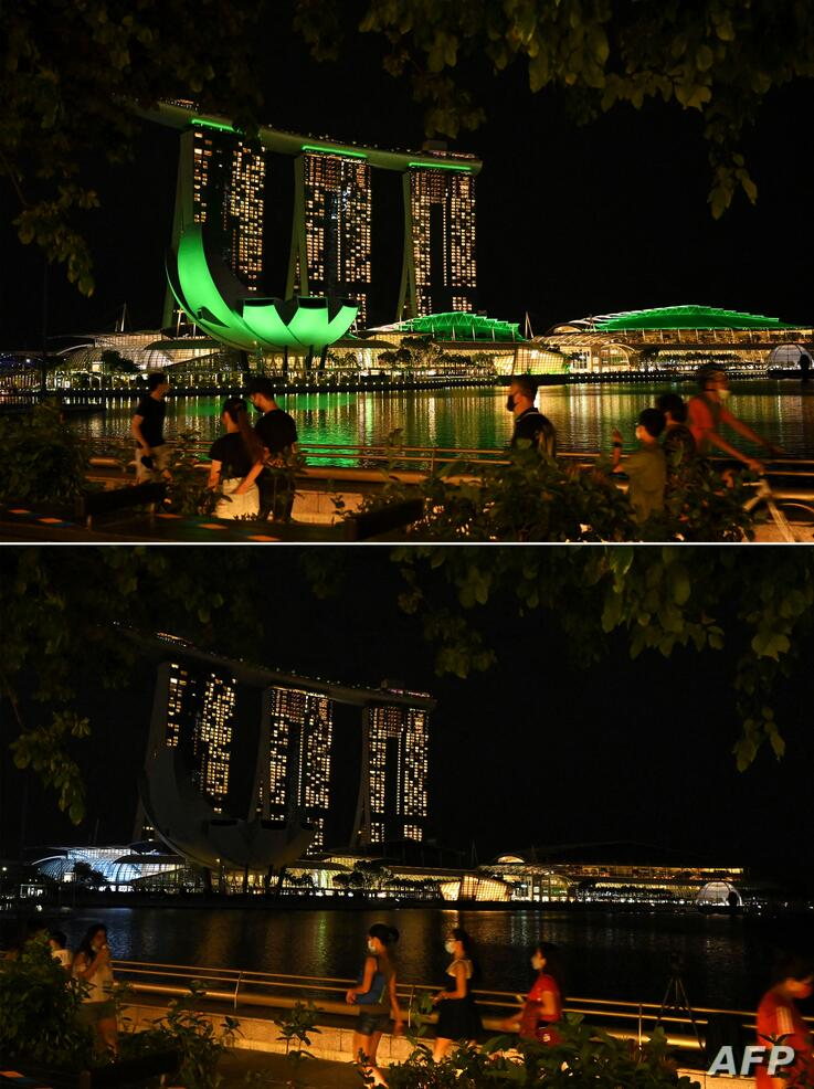 (COMBO) This combination of pictures created on March 27, 2021 shows a general view of the illuminated Marina Bay Sands hotel…