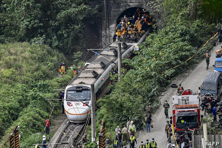 This photo shows rescue workers at the site where a train derailed inside a tunnel in the mountains of Hualien, eastern Taiwan…