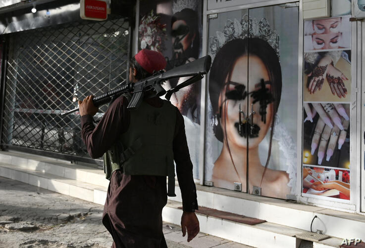 (FILES) In this file photo taken on August ۱۸, ۲۰۲۱, a Taliban fighter walks past a beauty salon with images of women defaced…