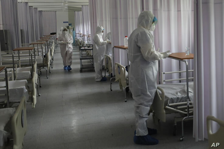 Medical staff wearing protective gear check tend to patients separated by privacy curtains, in the women's ward of a COVID-19…