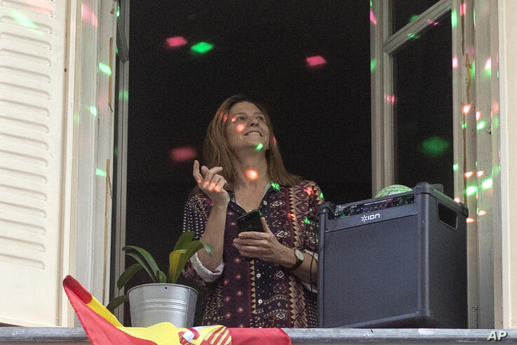 A woman stands by her open window while playing amplified music and with disco lights, as the lockdown to combat the spread of…