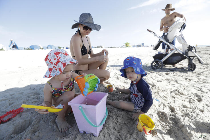 Ella, left 4 and her brother Dani, 3 play in the sand as their parents Natallia and Dan Victor watch, Wednesday, June 10, 2020,…