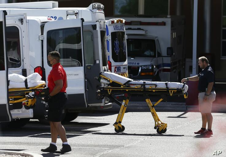 Medical transports and ambulances are parked outside the emergency-room entrance at Banner Desert Medical Center, Tuesday, June…