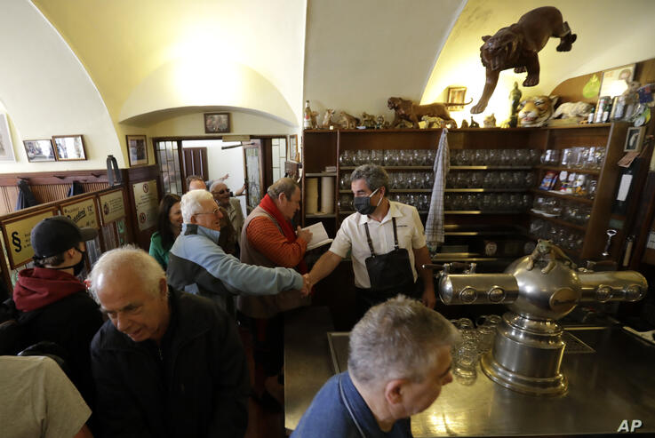 A bartender greets with a customer as a traditional beer pub opens in Prague, Czech Republic, Monday, May 25, 2020. The bars,…