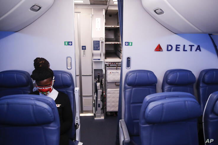 A Delta Airlines employee wears personal protective equipment after landing at Minneapolis−Saint Paul International Airport,…