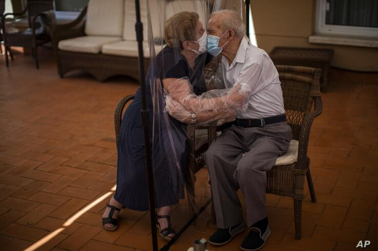 In this Monday, June 22, 2020 photo, Agustina Canamero, 81, and Pascual Pérez, 84, hug and kiss through a plastic film screen…