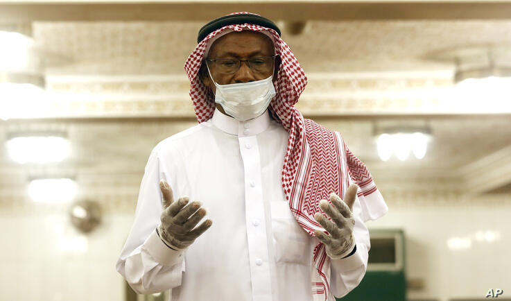 A Saudi worshipper wearing a face mask and gloves as he prays dawn prayers at al-Mirabi Mosque in Jiddah, Saudi Arabia, Sunday,…