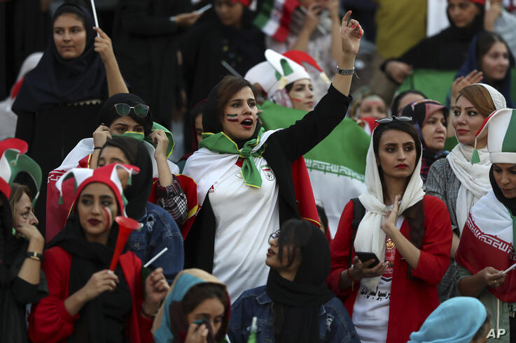 Iranian nurse Zahra Pashaei, center, cheers during an Iran and Cambodia 2022 World Cup qualifier soccer match at the Azadi …