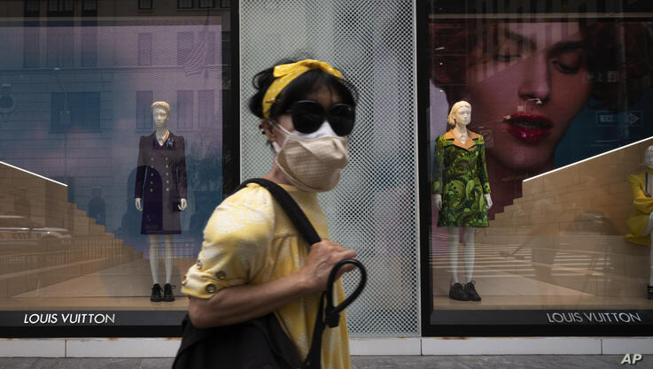 A woman wearing a mask walks by a Louis Vuitton store, Thursday, June 11, 2020, in New York's Fifth Avenue shopping district…