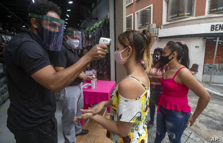 A mask-wearing shopper gets her temperature checked before entering a store in a downtown shopping district in Sao Paulo,…