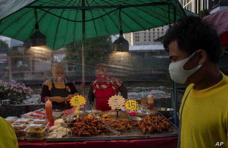 Street food venders stand behind a plastic sheet in Bangkok, Thailand, Tuesday, June 9, 2020. Daily life in capital resuming to…