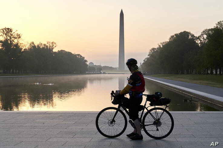 A cyclist at the Lincoln memorial Reflecting Pool watches the sun rise over the Washington Monument and National Mall as COVID…