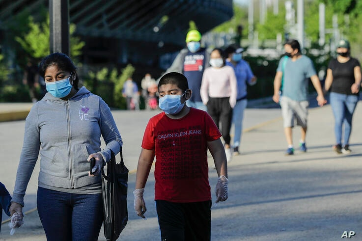 Pedestrians wear protective masks during the coronavirus pandemic as they enjoy warm weather in Flushing Meadows Corona Park,…