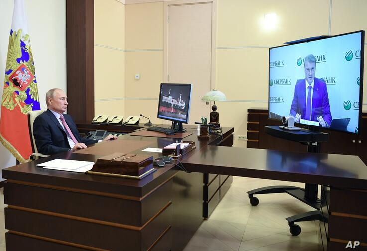 Russian President Vladimir Putin attends a meeting with Sberbank chairman German Gref via video conference at the Novo-Ogaryovo…