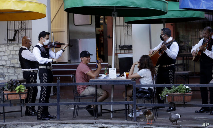 Mariachi Mexicanisimo play for diners at Casa Rio after it reopened in San Antonio, Monday, May 18, 2020. Texas Gov. Greg…