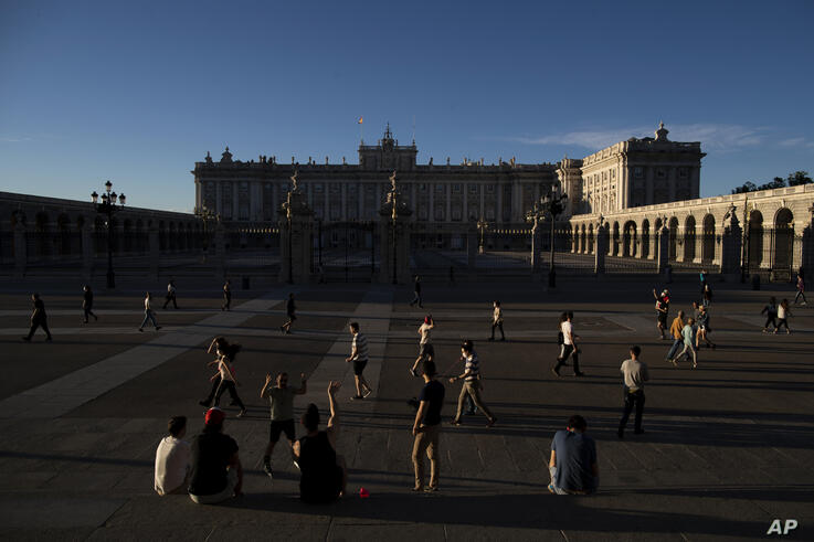 People walk keeping social distancing to prevent the spread of coronavirus around the Royal Palace in Madrid, Spain, Tuesday,…