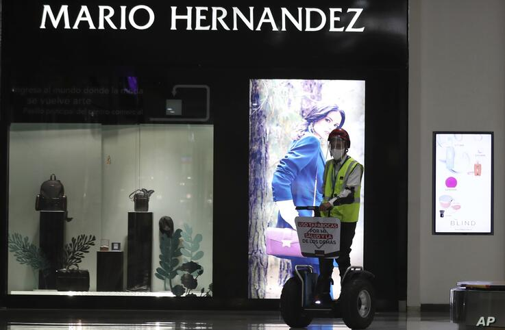A security guard patrols the Grand Station mall during a pilot program to test the reopening of the shopping center in Bogota,…