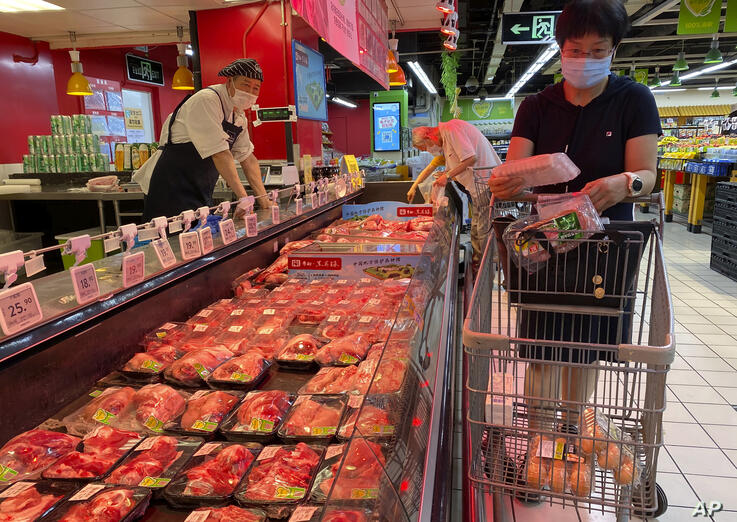 A resident wearing a face mask to curb the spread of the coronavirus browses meat products at a supermarket in Beijing, Monday,…