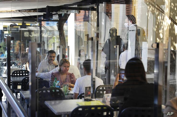 A man wearing a mask to curb the spread of the new coronavirus is reflected on a window as patrons talk inside a restaurant in…