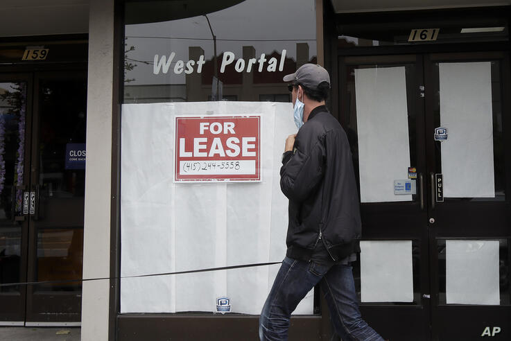 A man wearing a mask walks past a For Lease sign posted on the window of a storefront during the coronavirus outbreak in San…