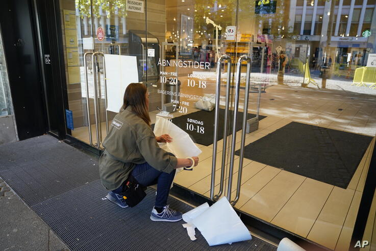 A worker from a department store prepares for its reopening in Aalborg, Denmark, Monday May 11, 2020, after the easing of the…