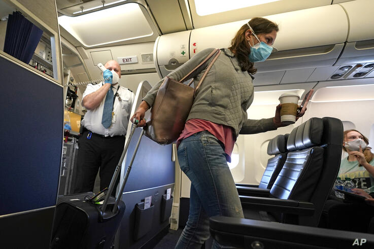 A passenger wears a mask while boarding a United Airlines flight at George Bush Intercontinental Airport Sunday, May 24, 2020,…