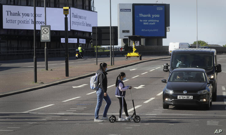 Pedestrians cross the road passing traffic as the country continues in lockdown to help stop the spread of coronavirus, Tuesday…