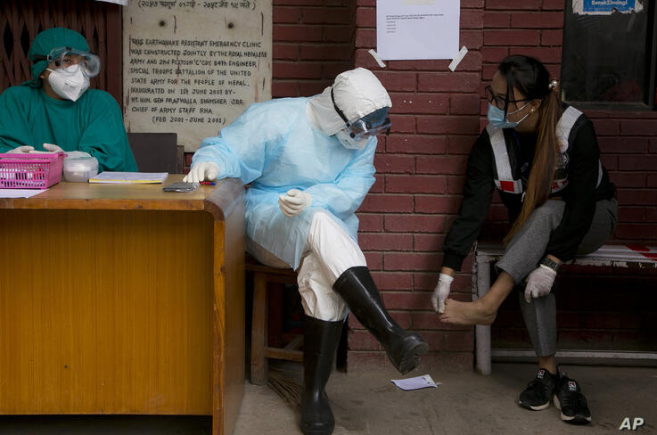 Punam Karmacharya, 22, of the RNA-16 volunteer group, consults with a doctor about the pain on her feet at a hospital in…
