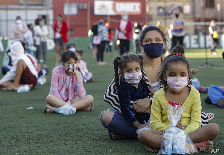 Residents sit on a soccer field as they wait to receive kits equipped with cleaning products and protective face masks for…