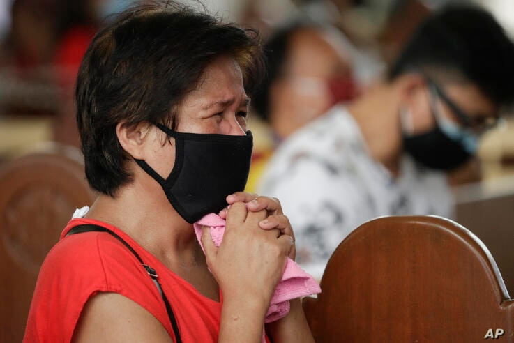 A devotee cries as she prays inside the Minor Basilica of the Black Nazarene, popularly known as Quiapo church, as it slowly…