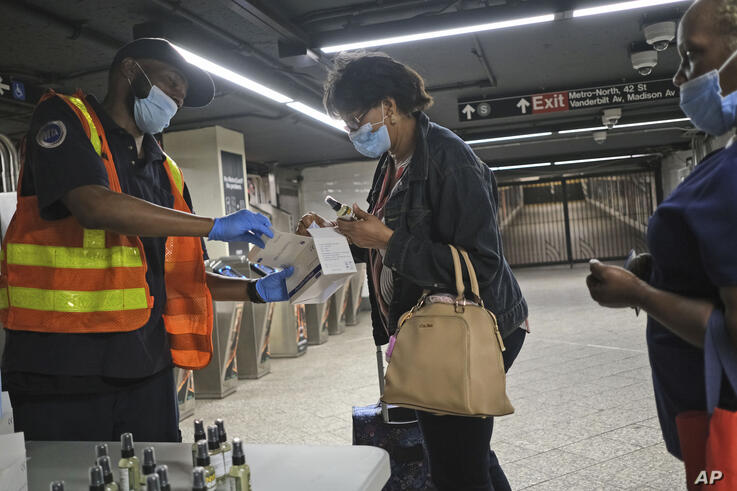 MTA employee Shawn Turner, left, gives away masks and hand sanitizer at the entrance to a subway station in New York, Monday,…
