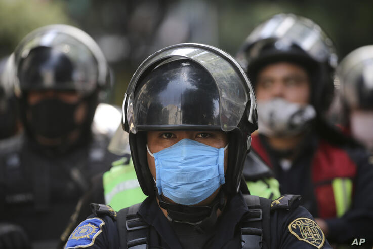 Polie wearing masks amid the new coronavirus pandemic stand guard during a protest outside Mexico City's security headquarters,…