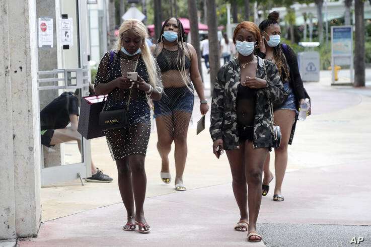 Shoppers wear protective face coverings as they walk along Lincoln Road Mall during the new coronavirus pandemic, Wednesday,…