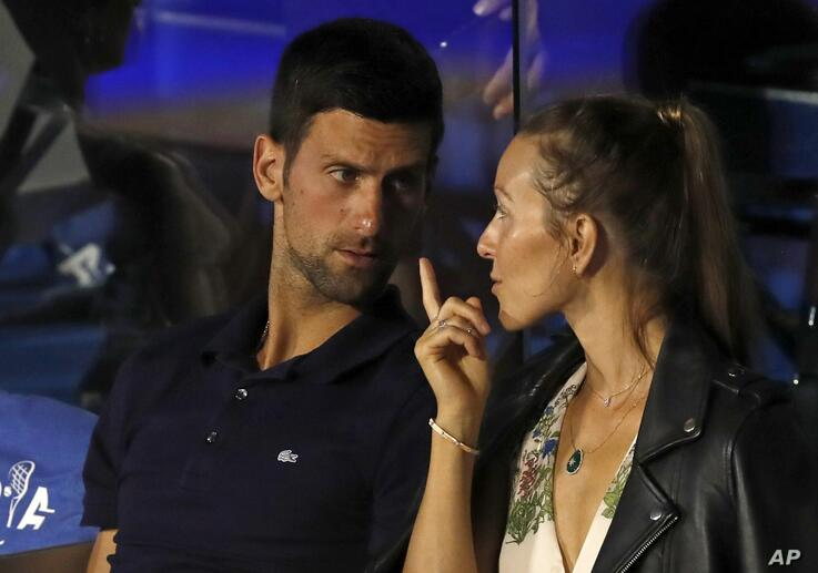 FILE - In this Sunday, June 14, 2020 file photo Serbia's Novak Djokovic, left, speaks with his wife Jelena during a final match…