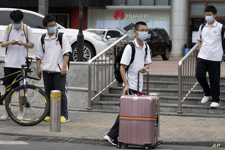 A student pushes a suitcase of his belongings from school after classes were cancelled in Beijing on Wednesday, June 17, 2020…